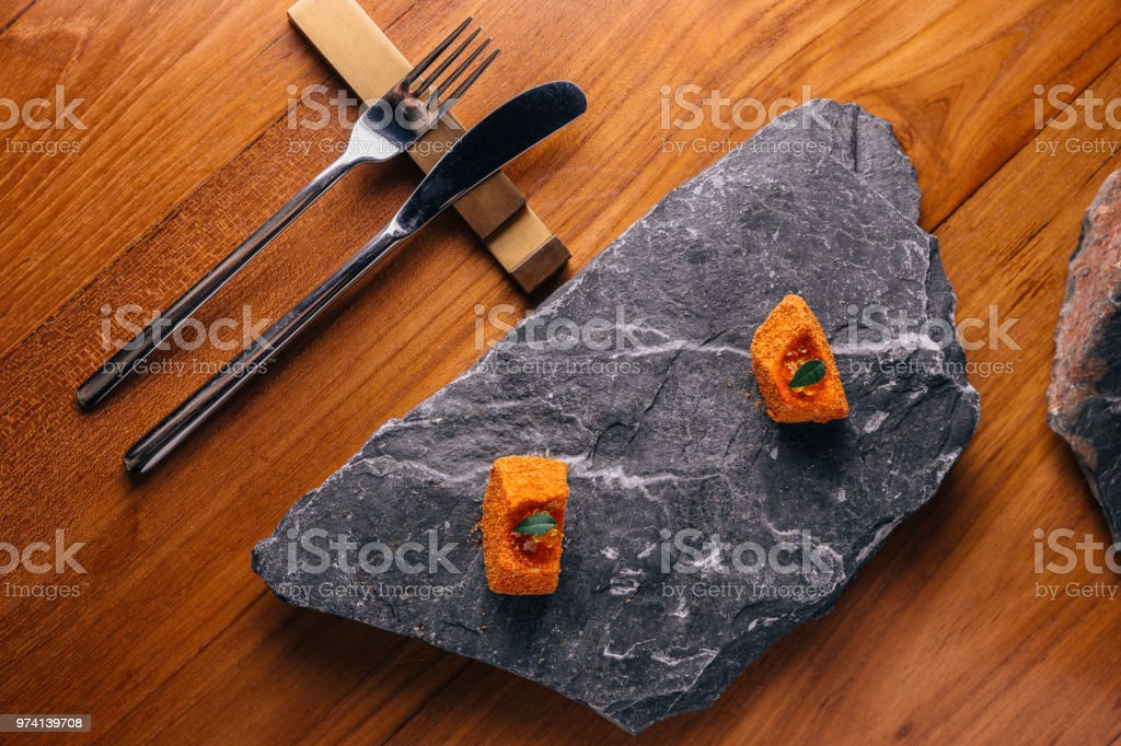 Fish with orange colour glaze topping with ikura served on stone...