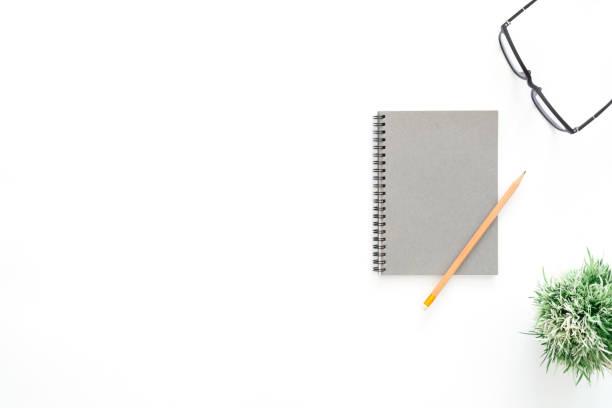 Kreatives FlachgelotoPhoto des Arbeitsraumes. Blick auf den Schreibtisch mit Brille, Bleistift, leerem Notizbuch und Pflanze auf weißem Farbhintergrund. Topansicht mit Kopierraum, Flach-Lay-Fotografie. – Foto