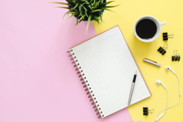 Kreative Wohnung liegen Foto von Arbeitsplatz Schreibtisch. Top-View Büroschreibtisch mit Mock-up-Notebooks, Pflanze, Kaffeetasse und Kopierplatz auf Pastell-Farbhintergrund. Top-Ansicht mit Kopierraum, flache Laienfotografie. – Foto