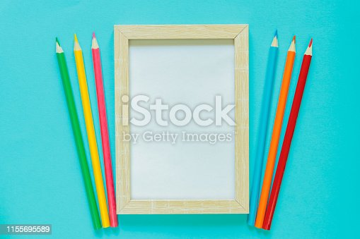 istock Creative flat lay with school suppllies. Mock up frame and multicolored pencils on blue background. Back to school. 1155695589