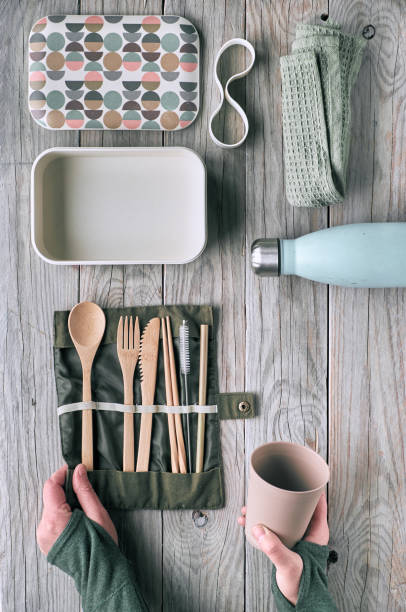 Creative flat lay, zero waste lunch concept with set of reusable wooden cutlery, lunch box, drinking bottle and reusable coffee cup. Sustainable lifestyle top view, flat layout on aged wood. stock photo