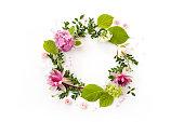 創造的なフラワーアレンジメント。花が咲き、葉と白い背景の上の花びらを持つフレームをラウンドします。フラット横たわっていた、トップ ビュー