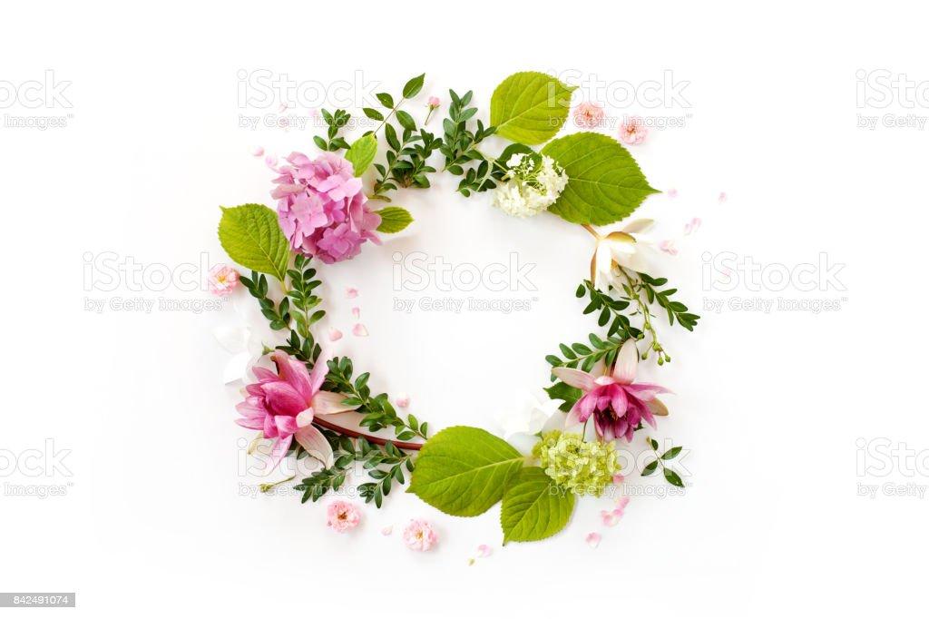 kreativa blomsterarrangemang. Rund ram med blommande blommor, blad och kronblad på vit bakgrund. platt lekmanna, top view bildbanksfoto