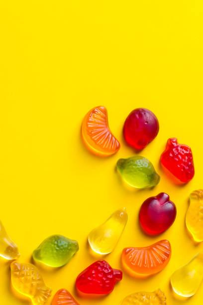 Kreative Food-Plakat-Bannerkartenvorlage. Gummigelee-Bonbons in Form von verschiedenen Sommer-und tropischen Früchten, die nach Muster auf gelbem Hintergrund angeordnet sind. Vitamine Kids Geburtstags-Spaß-Konzept – Foto