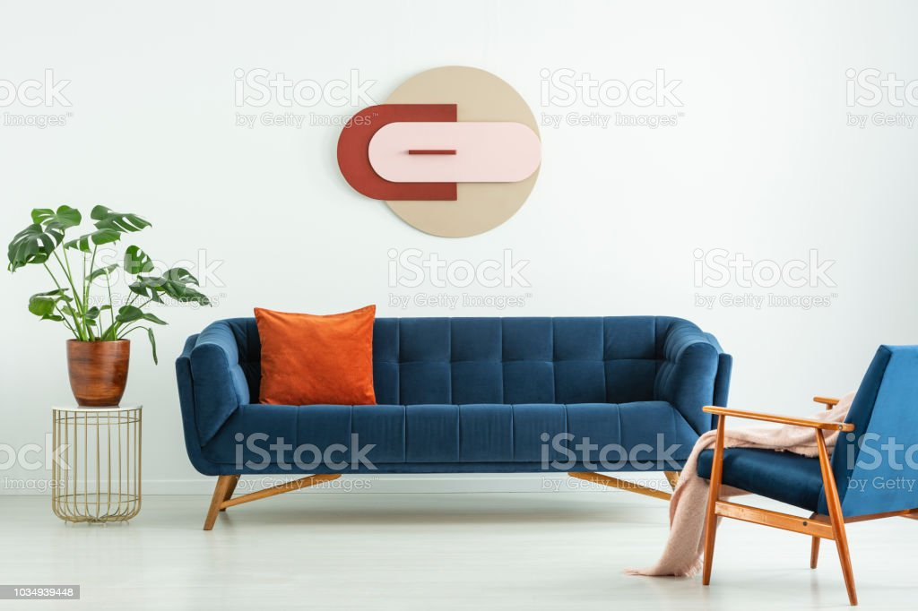 Creative geometric art on a white wall above an elegant blue sofa in a mid-century modern style living room interior. Real photo. stock photo