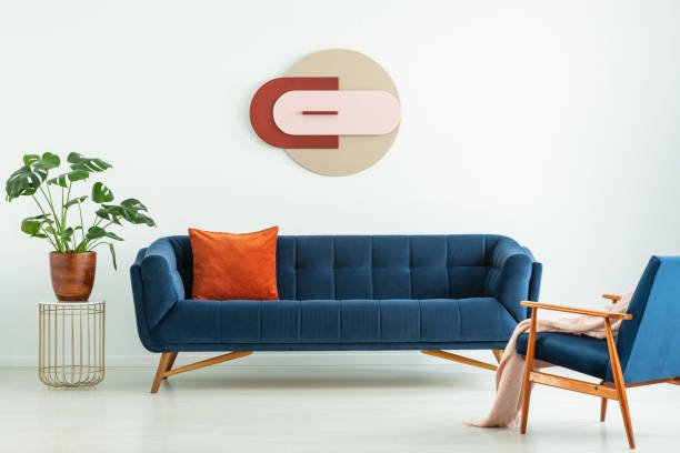 creative geometric art on a white wall above an elegant blue sofa in a mid-century modern style living room interior. real photo. - midcentury design stock photos and pictures