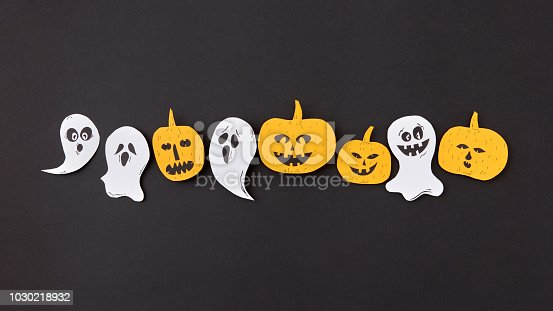 istock Creative handmade application with pattern of terrible spirits smiling and laughing the pumpkin on a black background. 1030218932