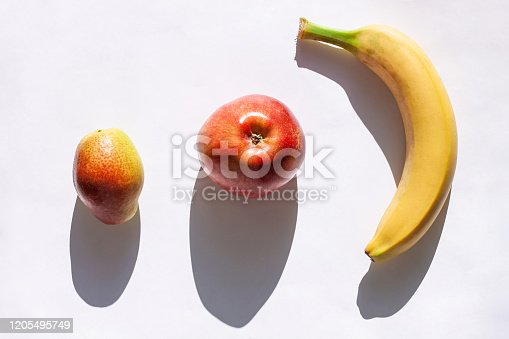 1176496357 istock photo Creative healthy breakfast concept on a white background flat lay. Fresh banana, apple, pear fruits with natural shadow. 1205495749