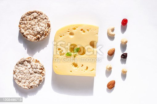 1176496357 istock photo Creative healthy breakfast concept white background flat lay.Cheese,calcium rich food,nut, fruit, whole grain crispbread 1205495713