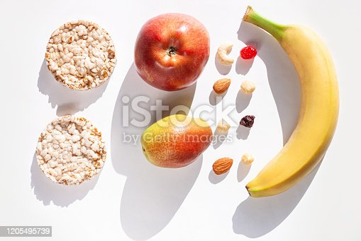 1176496357 istock photo Creative healthy breakfast concept white background flat lay.Cheese,calcium rich food,nut, fruit, whole grain crispbread 1205495739