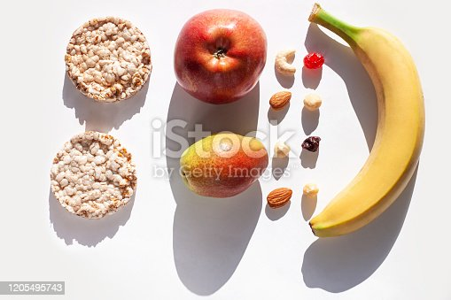 1176496357 istock photo Creative healthy breakfast concept white background flat lay.Cheese,calcium rich food,nut, fruit, whole grain crispbread 1205495743