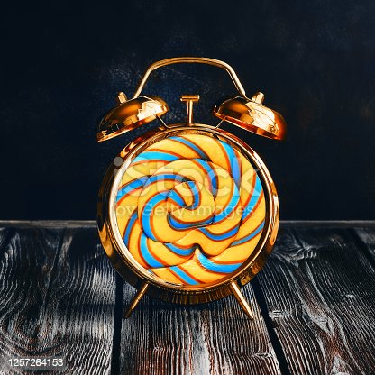 Creative idea alarm clock with swirl lollipop on rustic dark wooden table. Holiday, business or advertising concept. Modern minimal still life