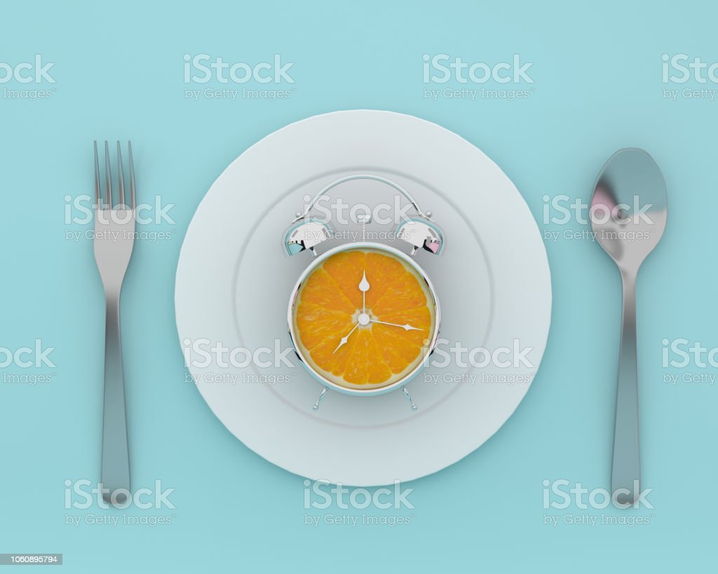 Creative idea layout made of fresh orange slice alarm clock on plate with spoons and forks on blue color background. minimal healthcare concept. stock photo