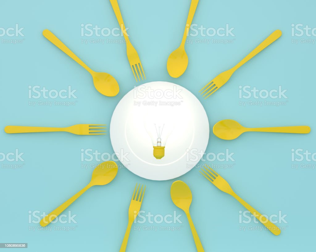 Creative idea layout made of yellow light bulbs glowing on plate with spoons and forks on blue color background. minimal healthcare concept. stock photo