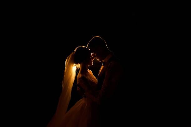 Creative idea of wedding photography at night. Silhouette of a bride and groom illuminated by a lights stock photo