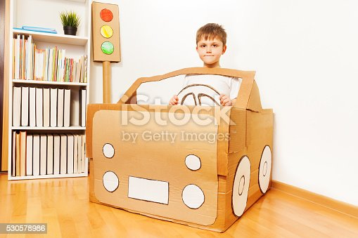 496487362 istock photo Creative kid boy plays with his cardboard car 530578986