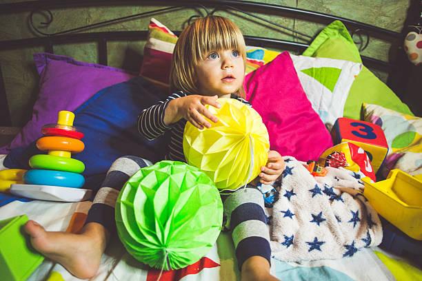 creative kid playing in bed - lila, grün, schlafzimmer stock-fotos und bilder
