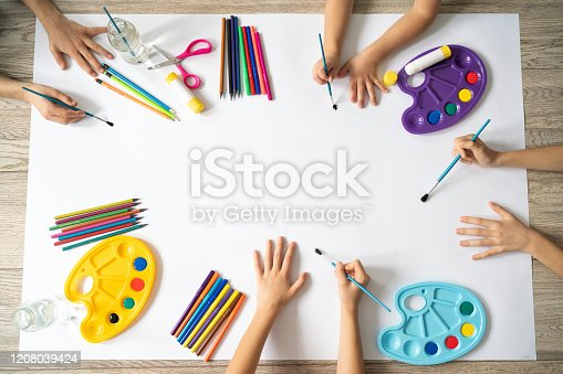 Top view of childrens hands over background with art supplies