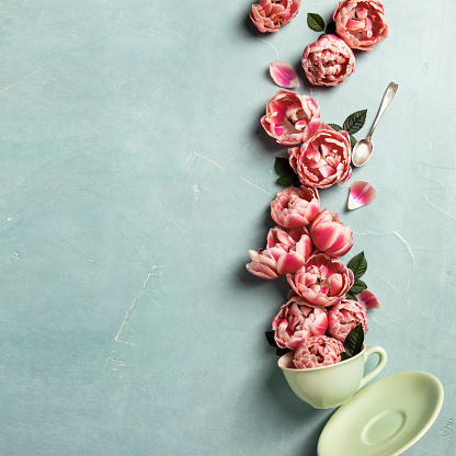 Creative layout made of coffee or tea cup with pink flowers on blue background, flat lay