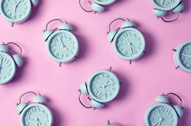 Creative layout of blue alarm clock's on pastel pink background. Minimal concept