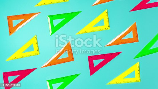 istock Creative layout of school supplies neon colors square rulers pattern against pastel blue background. 1155223315