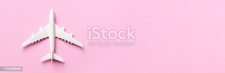 istock Creative layout. Top view of white model plane, airplane toy on pink pastel background. Flat lay with copy space. Trip or travel banner 1155398582