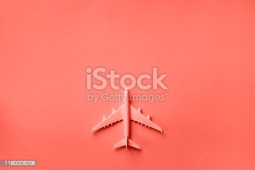 istock Creative layout. Top view of white model plane, airplane toy on pink pastel background. Flat lay with copy space. Trip or travel banner in trendy coral color 1160028206