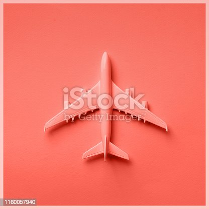 istock Creative layout. Top view of white model plane, airplane toy on pink pastel background. Flat lay with copy space. Trip or travel banner in trendy coral color 1160057940