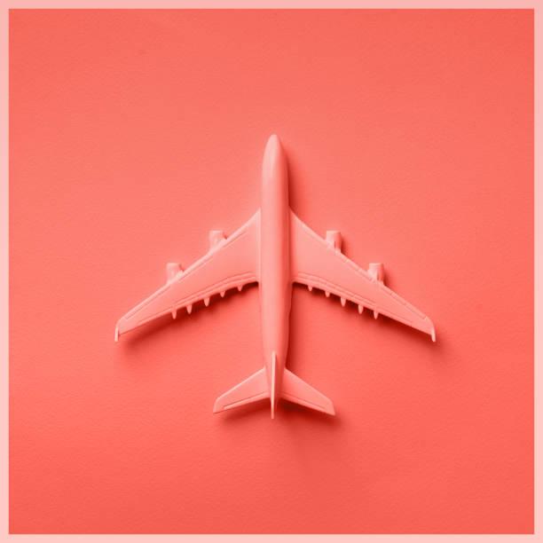 mise en page créative. vue supérieure du plan blanc de modèle, jouet d'avion sur le fond pastel rose. plat gisait avec l'espace de copie. drapeau de voyage ou de voyage dans la couleur de corail à la mode - monochrome image teintée photos et images de collection