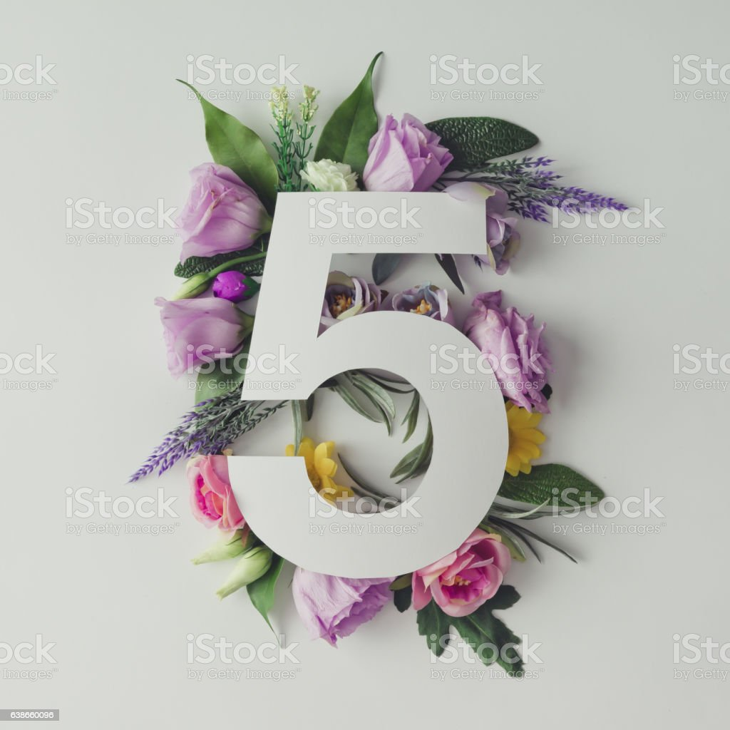 Creative layout with colorful flowers, leaves and number five. A stock photo