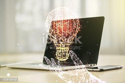 istock Creative light bulb hologram on modern laptop background, idea concept. Multiexposure 1223133102