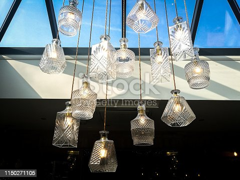 Color image depicting a collection of interesting indoor lights whose shades have been made out of upcycled glass, namely wine and whisky decanters. Room for copy space.