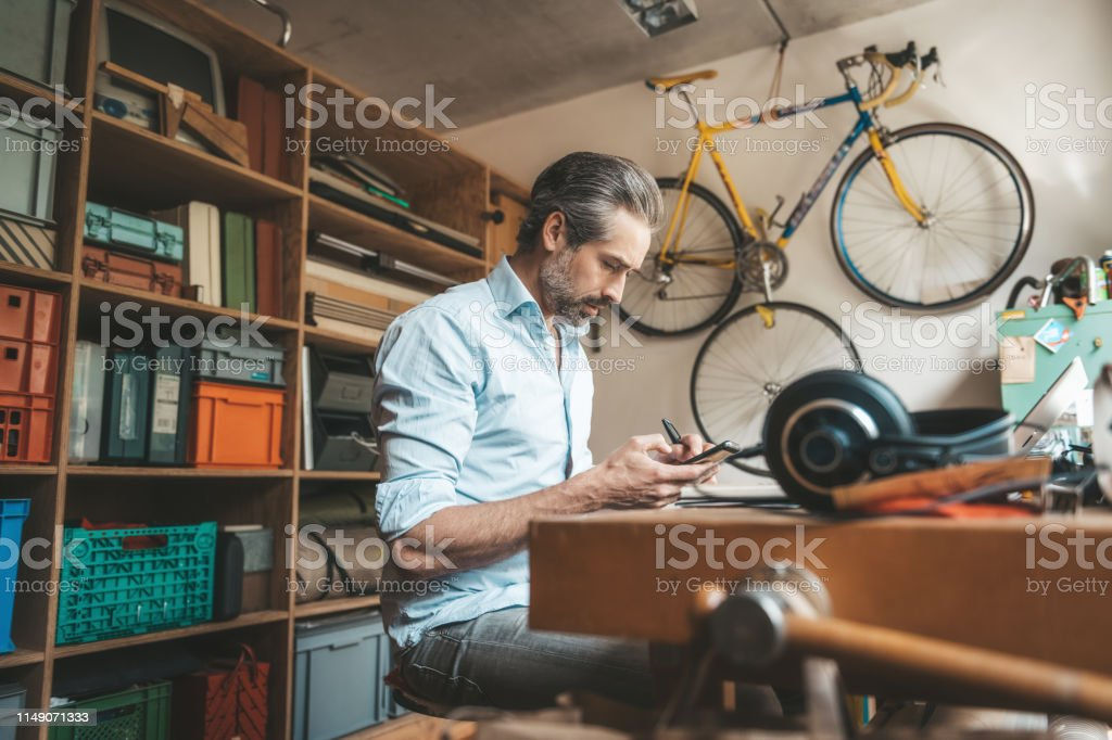 handsome creative man tapping at mobile in home office
