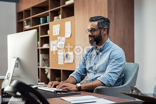 Smiling creative business man typing on desktop computer in office. Mature middle eastern businessman working at modern office space. Happy hispanic man wearing casual and eyeglasses working on his computer.