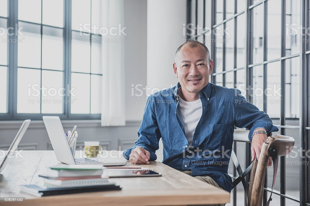 Creative mature man at desk in modern office bildbanksfoto