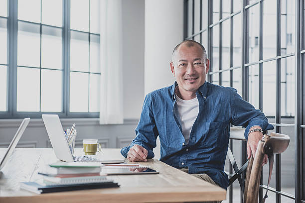 Creative mature man at desk in modern office stock photo