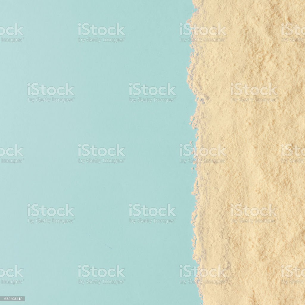 Creative minimal beach concept. Summer vacation layout with sand on blue background. Flat lay. stock photo