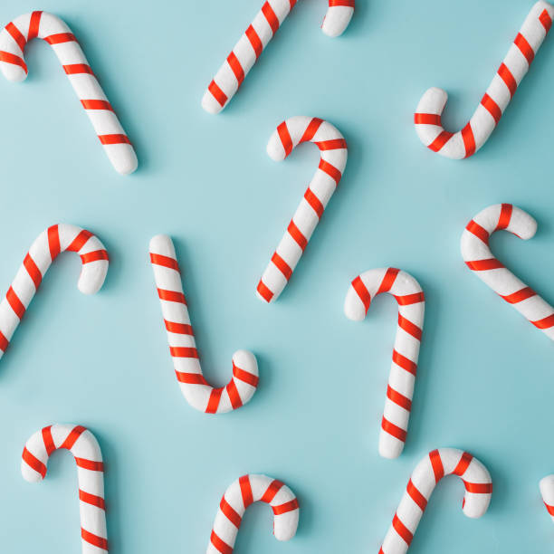 Creative minimal Christmas art. Pattern made with Christmas candies on bright blue background. Flat lay. Copy space. Minimal composition. candy cane stock pictures, royalty-free photos & images