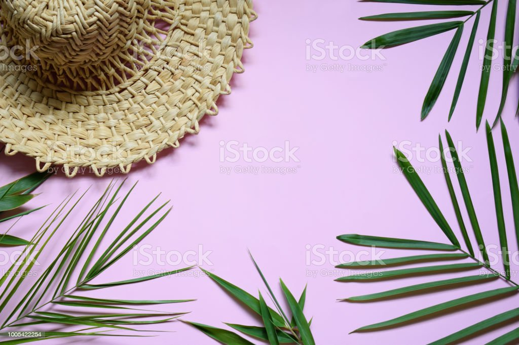 Creative minimal summer idea. Tropical beach concept made of bamboo hat, seashells and green palm leaves on pastel background. Creative art. Flat lay, top view. Copy space stock photo