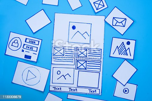 1182469817 istock photo Creative mobile responsive website designer sorting wireframe screens of mobile application process development prototype wireframe. User experience concept. 1133306679