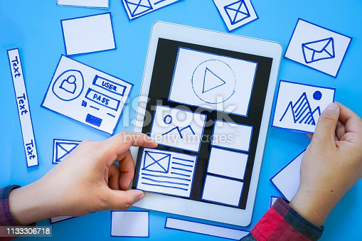 1182469817 istock photo Creative mobile responsive website designer sorting wireframe screens of mobile application process development prototype wireframe. User experience concept. 1133306718