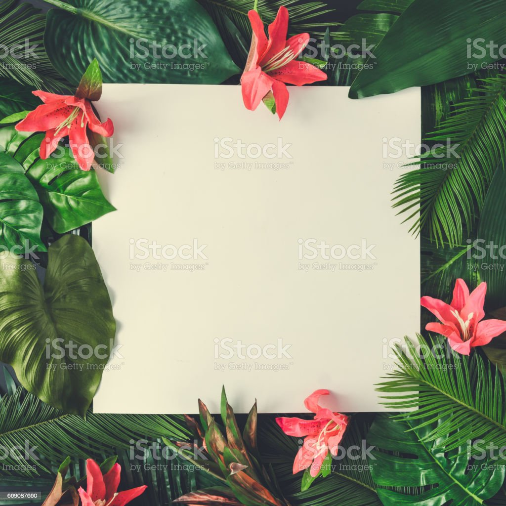 Creative nature layout made of tropical leaves and flowers With paper card note. Flat lay. Summer concept. stock photo