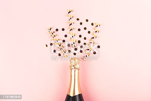 1051699126 istock photo Creative New Year composition with champagne bottle and confetti on pastel pink background. 1191982845