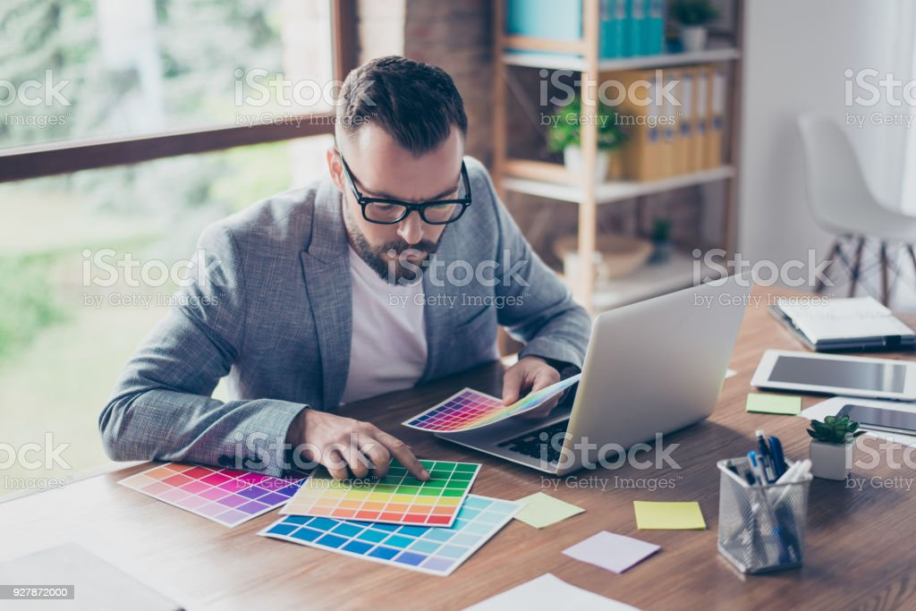 Creative occupation, making decision. Close up of stylish bearded male architect with  mustache in trendy specs and grey formal jacket, choosing the colors for new project, looking at the pantone стоковое фото