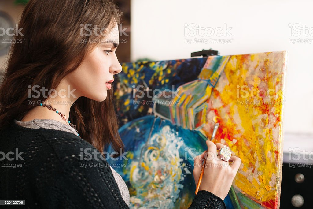 Creative painter paints colorful picture. Closeup stock photo