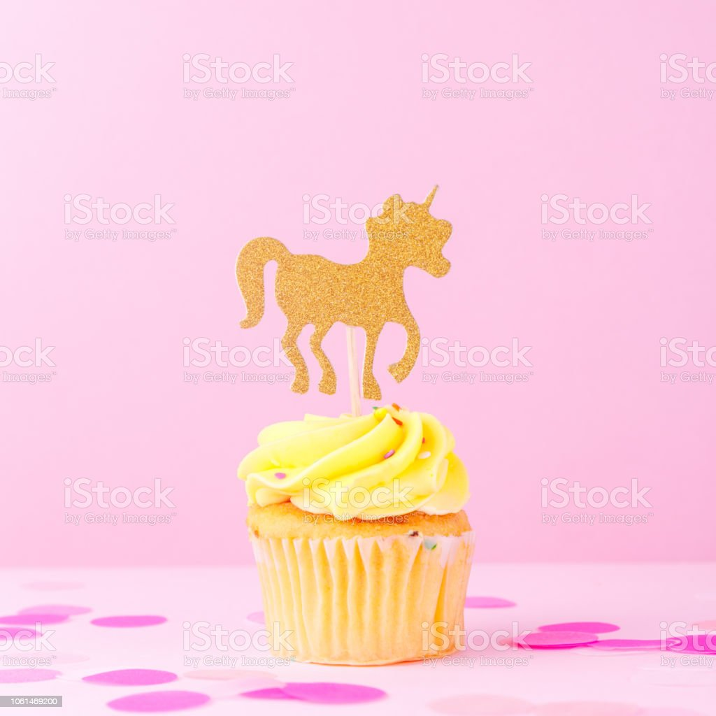 Creative pastel fantasy holiday card with cupcake, confetti and unicorn. Baby shower, birthday, celebration concept. stock photo
