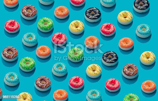 istock Creative pattern of colorful donuts on pastel blue background. Minimal food concept. Isometric. 985115260