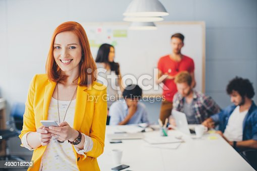 Red hair woman  posing and looking at camera in front. She is using smart phone and smiling. Her colleagues collaborating behind by the table. Multi-Ethnic Group. Wearing casual clothes.