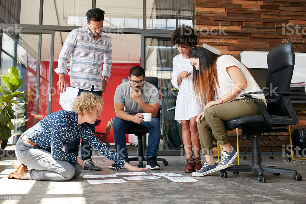 Creative people looking at project plan laid out on floor stock photo