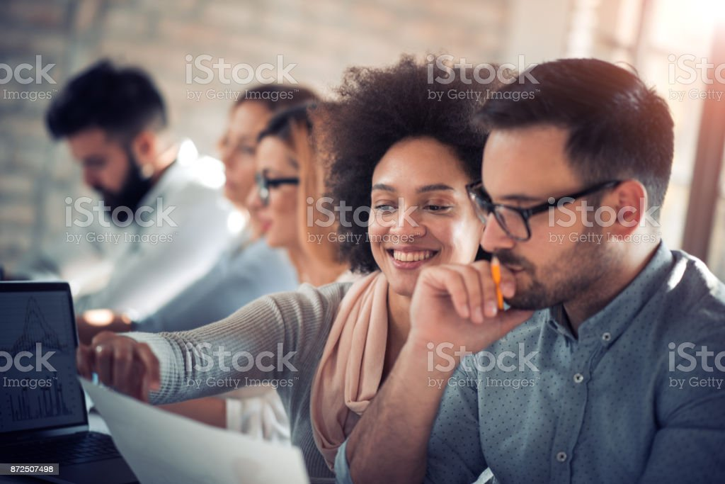 Creative people working in office on computer stock photo